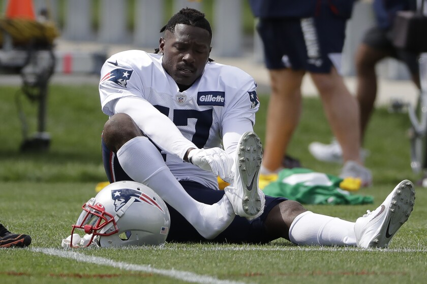 New England Patriots wide receiver Antonio Brown puts on his shoe during an NFL football practice, Wednesday, Sept. 18, 2019, in Foxborough, Mass. (AP Photo/Steven Senne)