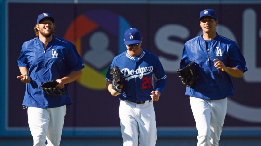 Dodgers pitchers Clayton Kershaw, Scott Kazmir and Rich Hill jog together before a game against the Phillies on Aug. 9.