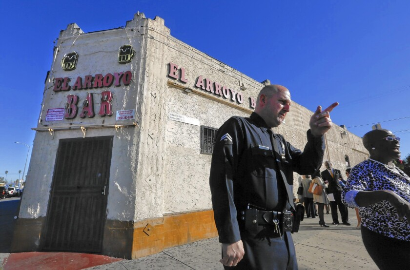 LAPD Officer Justin Fuller speaks with community members before the announcement of the city's closure of the El Arroyo Bar in South Los Angeles on Tuesday.