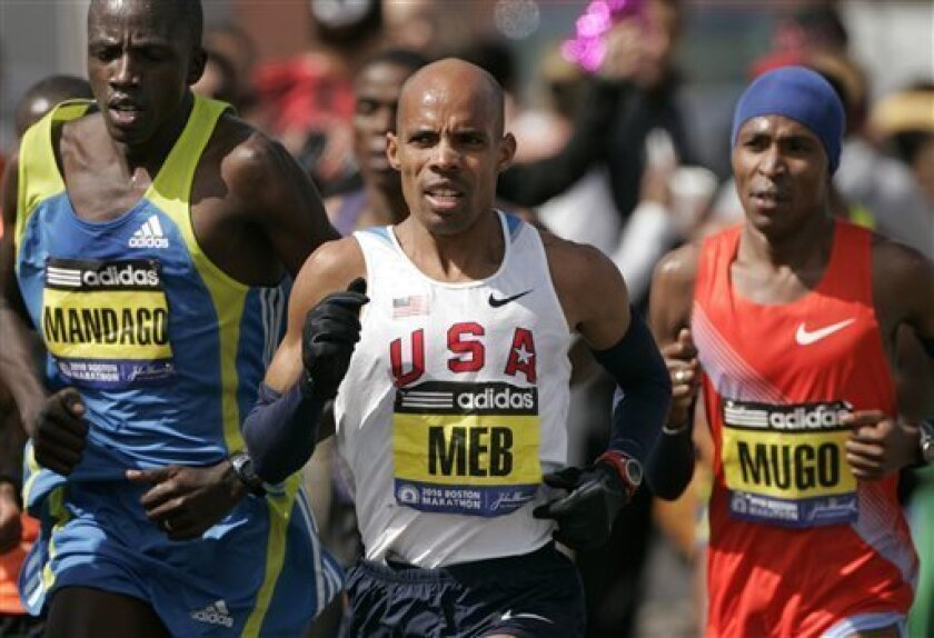 Mebrahtom Keflezighi, of Mammoth Lakes, Calif., center, runs along side David Mandago, of Kenya, left, and Samuel Mugo, also of Kenya, right, in the Natick, Mass., portion of the Boston Marathon, Monday, April 19, 2010. Keflezighi went on to finish fifth in the 26.2 mile race Monday. (AP Photo/Steven Senne)