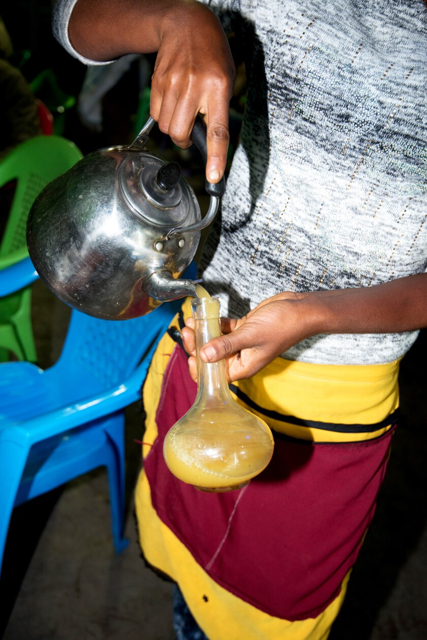 Pouring a glass of tej, honey wine, at Berkay Tej Bet in Lailibela, Ethiopia