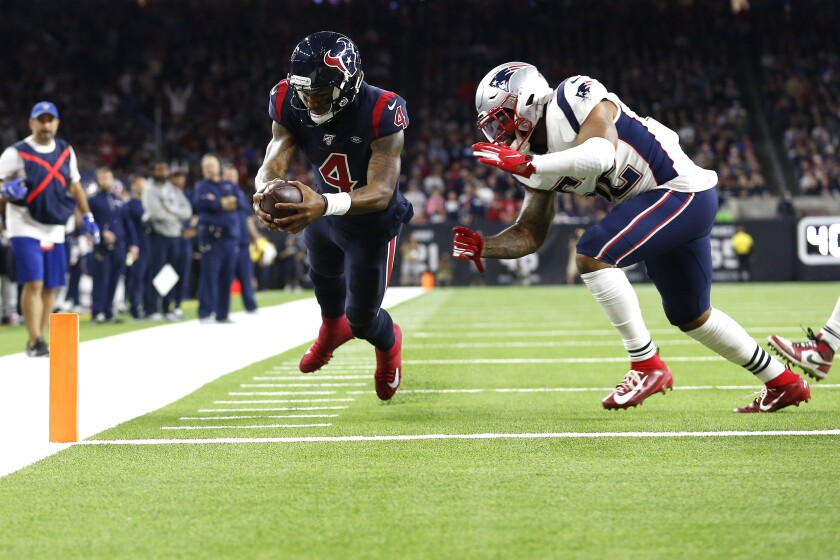 Houston Texans quarterback Deshaun Watson scores a touchdown in front of New England Patriots linebacker Elandon Roberts.