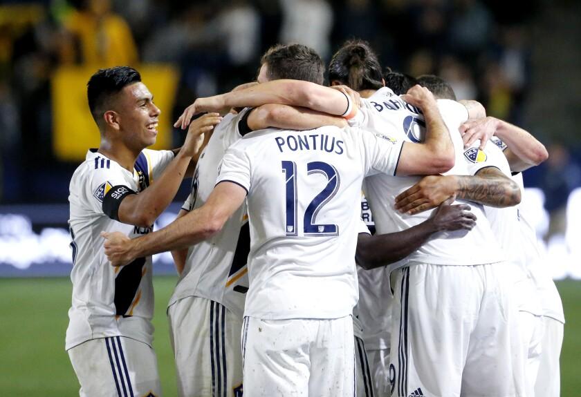 Galaxy midfielder Efrain Alvarez joins teammates celebrating their their goal against Sporting Kansas City.