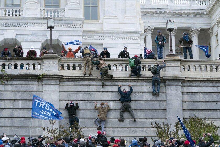 FILE - In this Jan. 6, 2021 file photo, violent insurrectionists loyal to President Donald Trump scale the west wall of the the U.S. Capitol in Washington. In the nearly nine months since Jan. 6, federal agents have managed to track down and arrest more than 600 people across the U.S. believed to have joined in the riot at the Capitol. Getting those cases swiftly to trial is turning out to be an even more difficult task. (AP Photo/Jose Luis Magana, File)