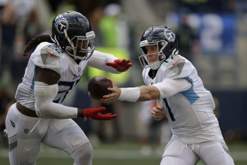 El quarterback de los Titans de Tennnessee Ryan Tannehill le entrega el balón al corredor Derrick Henry en la segunda mitad del encuentro ante los Seahawks de Seattle el domingo 19 de septiembre del 2021 en Seattle. (AP Foto/John Froschauer)