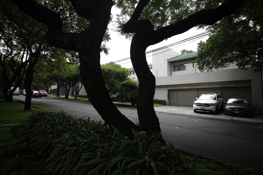 Dos automóviles se encuentran estacionados frente a la casa de la exprimera dama Angélica Rivera en el vecindario Lomas de Chapultepec en la Ciudad de México, el viernes 19 de julio de 2019. (AP Foto/Rebecca Blackwell)