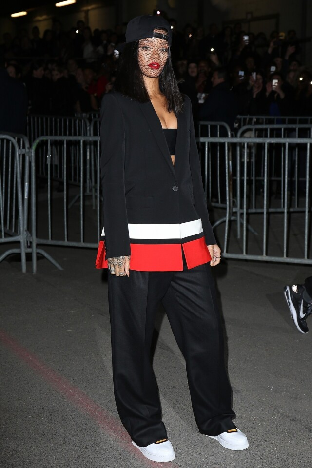 Rihanna wears a baggy pants suit by designer Riccardo Tisci to the Givenchy show at Paris Fashion Week.