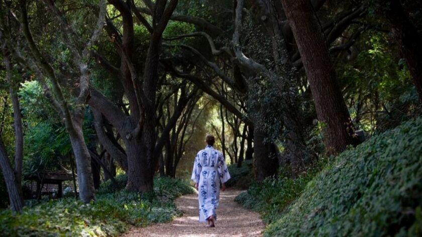 In a file photo, a kimono-wrapped woman walks through an archway of trees at the Golden Door in Twin Oaks Valley.