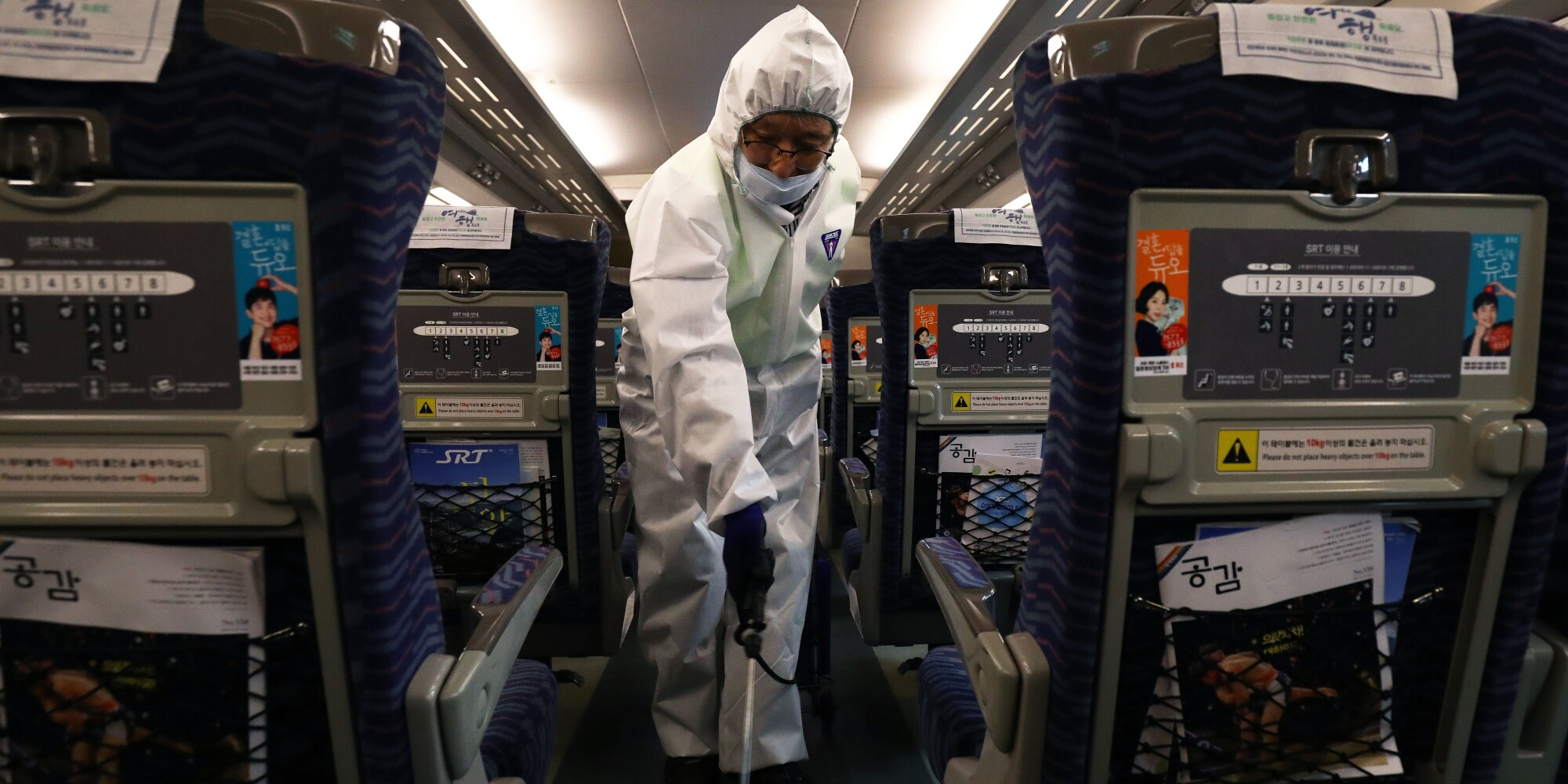 A disinfection worker wearing protective gear sprays antiseptic solution in a train at an SRT train station on Friday in Seoul amid rising public concerns over the spread of China's coronavirus.