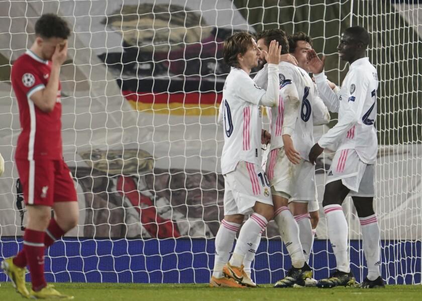 Diogo Jota, del Liverpool, se lamenta, mientras los jugadores del Real Madrid festejan, tras el partido de vuelta de los cuartos de final en la Liga de Campeones, el miércoles 14 de abril de 2021 (AP Foto/Jon Super)