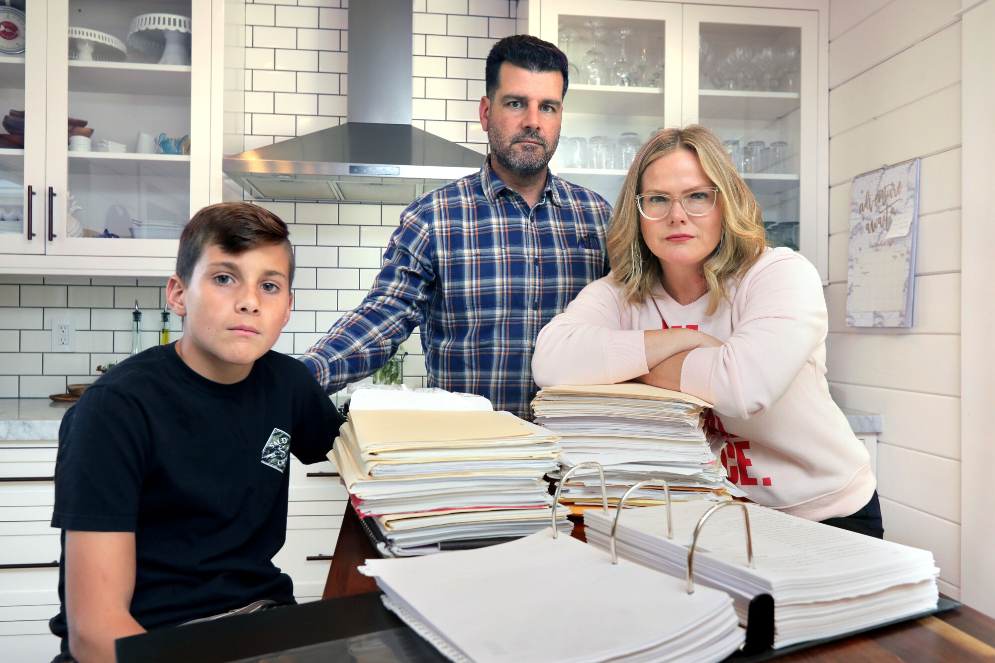 Diego Lazaro, 12, and his parents Oscar and Melissa Lazaro with all of the paperwork they've accumulated in their years-long effort to get Diego the education they feel he deserves with his dyslexia.