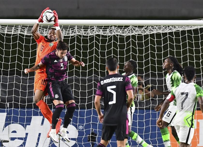 El portero de Nigeria Bobo Stanley Nawabili atrapa el balón frente al mexicano Carlos Salceto.