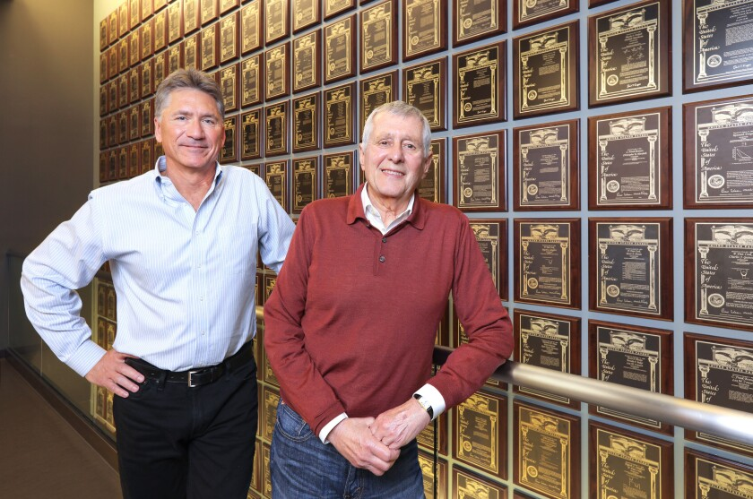 Portrait of Ionis Pharmaceuticals Chief Operating Officer Brett Monia, left, and CEO Stanley Crooke, at right, at the company's extensive patent wall. Brett will take over as CEO next year.