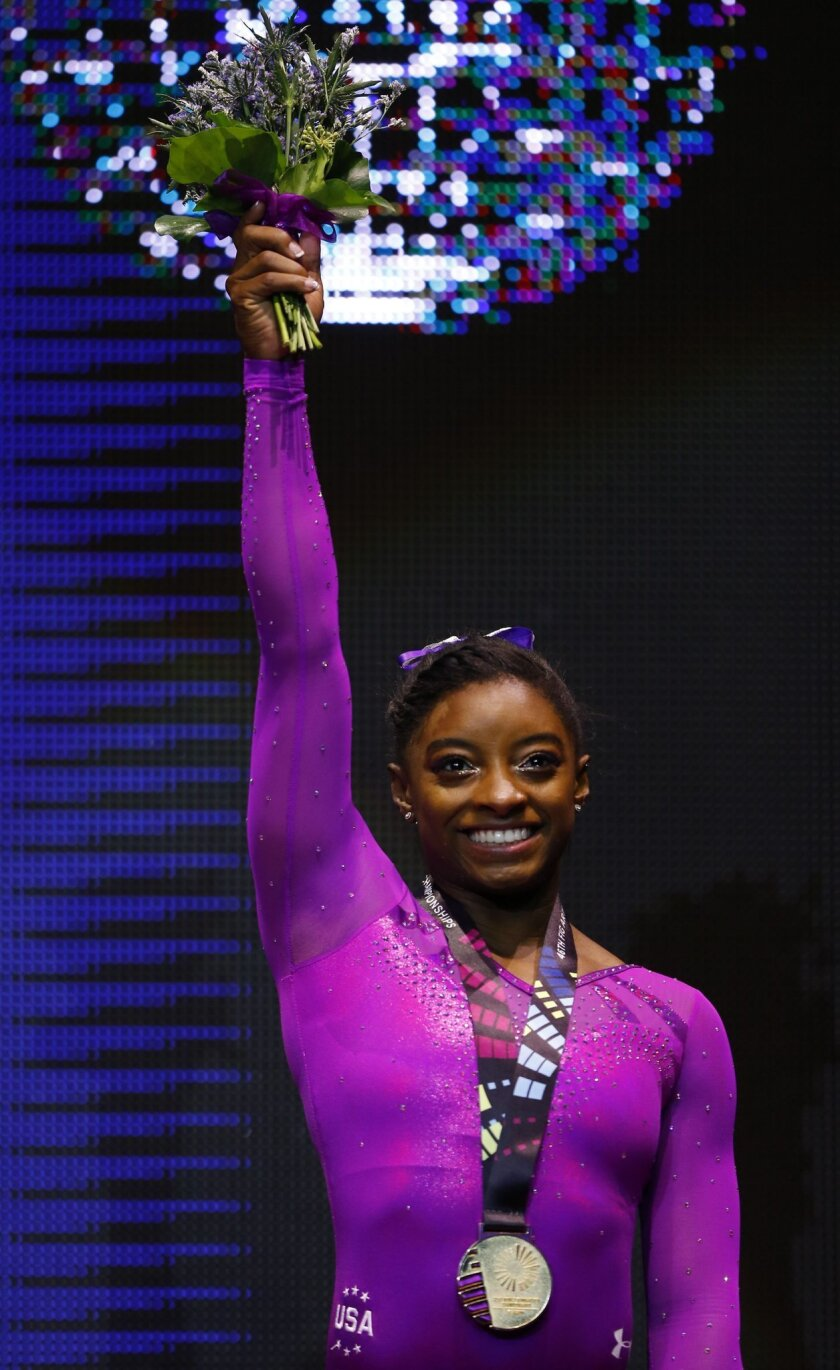 Gold medal winner Simone Biles of the U.S. poses on the podium after the floor exercise during the women's apparatus final competition at the World Artistic Gymnastics championships at the SSE Hydro Arena in Glasgow, Scotland, Sunday, Nov. 1, 2015. (AP Photo/Matthias Schrader)