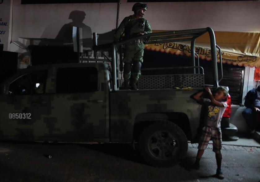 """Un menor observa agentes del Ejercito Mexicano patrullando las calles este jueves, 4 de enero de 2018, en Chilpancingo Guerrero (México). Los niños y adolescentes mexicanos sufrieron en 2017 un año """"terrible"""" al registrarse altas cotas de violencia y un nivel flagrante de impunidad, denunció hoy la Red por los Derechos de la Infancia en México (Redim). EFE"""