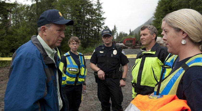 Alaska Gov. Bill Walker, left, talks with emergency workers at the landslide site on Kramer Ave. in Sitka, Alaska, Wednesday, Aug. 19, 2015. Three men missing in the slide were being searched for Wednesday. (James Poulson/Daily Sitka Sentinel via AP)