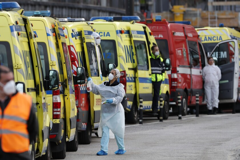 More than a dozen ambulances queue waiting to hand over their COVID-19 patients to medics at the Santa Maria hospital in Lisbon, Friday, Jan. 22, 2021. Portugal's COVID-19 surge is continuing unabated, with a new record of daily deaths, hospitalizations and patients in intensive care. (AP Photo/Armando Franca)