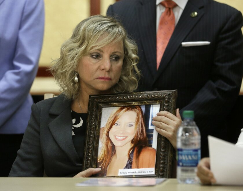Debbie Ziegler holds a photo of her daughter, Brittany Maynard, the California woman with brain cancer who moved to Oregon to legally end her life last fall, during a news conference to announce the reintroduction of right to die legislation, Tuesday, Aug. 18, 2015, in Sacramento,Calif.  The measur