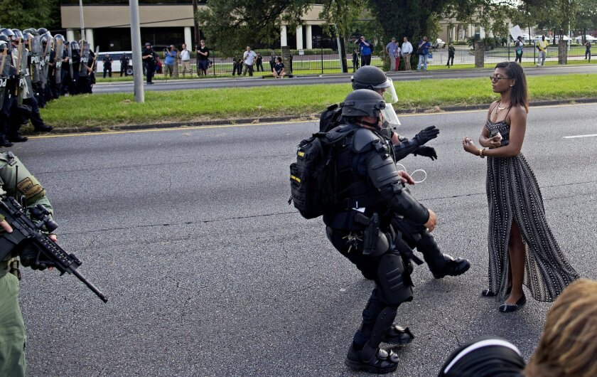 FILE In this Saturday, July 9, 2016 file photo, A protester is grabbed by police officers in riot gear after she refused to leave the motor way in front of the the Baton Rouge Police Department Headquarters in Baton Rouge, La. Police made nearly 200 arrests in Louisiana's capital city during weeken