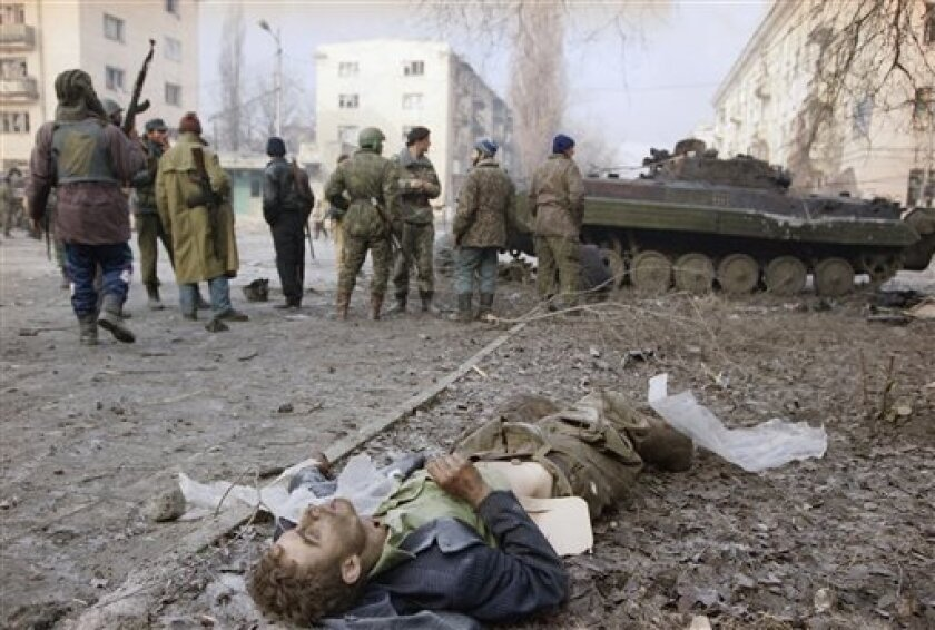 FILE - In this Jan. 3, 1994 file photo, a Russian soldier lies dead as Chechen fighters gather next to a tank outside the presidential palace in central Grozny, as Russian troops and Chechen fighters battled for control of the breakaway capital. Two suspects in the Boston Marathon bombing have been