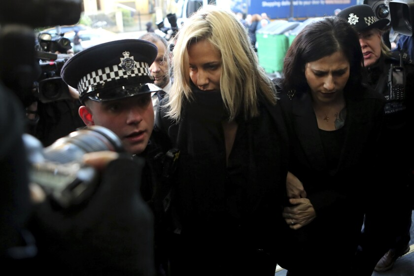 FILE - In this file photo dated Monday, Dec. 23, 2019, Love Island TV presenter Caroline Flack, centre, as she arrives at Highbury Magistrates' Court in London. A British coroner has ruled Thursday Aug. 6, 2020, that reality TV host Caroline Flack killed herself while facing an assault trial she feared would end her career and bring unbearable media scrutiny.(AP Photo/Petros Karadjias, FILE)