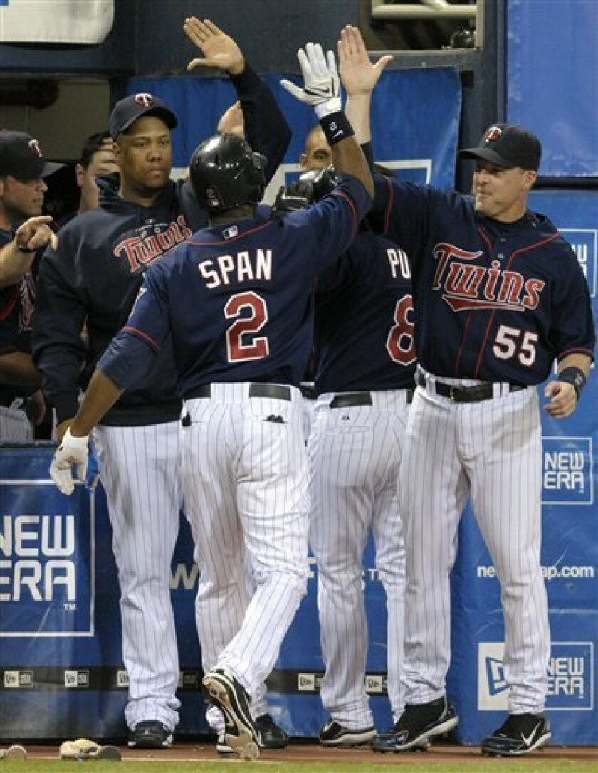 Minnesota Twins' Denard Span (2) is congratulated by teammates Livan Hernandez, left, and Mike Redmond, right, as he comes to the dugout after hitting a two-run home run during the third inning of a baseball game against the Chicago White Sox, Monday, July 28, 2008 in Minneapolis. (AP Photo/Tom Olmscheid)