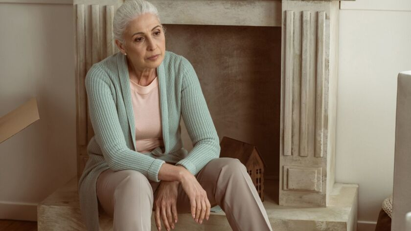 upset senior woman taking break from packing cardboard boxes, moving out concept