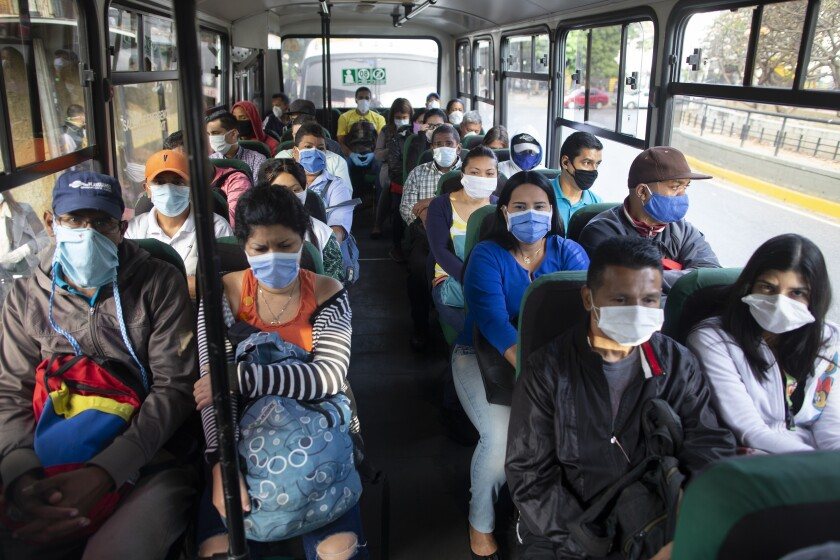 People wearing protective masks as a precaution against the spread of the new coronavirus travel on a bus in Caracas, Venezuela, Tuesday, March 17, 2020. President Nicolas Maduro ordered citizens to stay home, and to wear a mask in public under a quarantine in a bid to control the spread of the coronavirus. The vast majority of people recover from the new virus. (AP Photo/Ariana Cubillos)