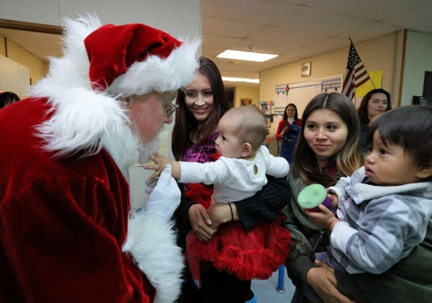 Six-month old Lexi Serrato, held by mom Natalie Serrato, 17, an Ocean Shores High School student, reaches for Santa's beard. At right is student Jacky De Dios with one and a half year old son Adrian.