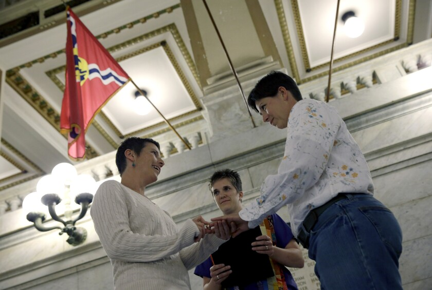 April Dawn Breeden, left, places a ring on the finger of her longtime partner Crystal Peairs, at their wedding in St. Louis on Wednesday, just after a state judge overturned Missouri's gay marriage ban.