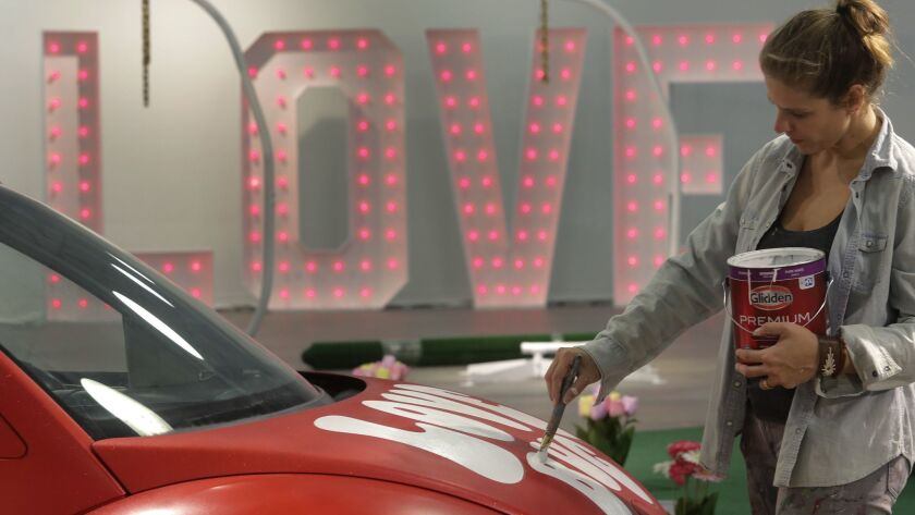 "Hanna Daly paints the words Love Bug on a red Volkswagen Beetle during final preparations Thursday morning for the pop-up exhibition ""Museum of Wha? Love Tour,"" which opened on Valentine's Day evening in Encinitas."