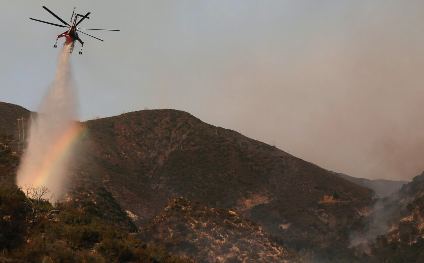 A firefighting helicopter makes a water drop on Sept. 23 during the Bobcat Fire in the Angeles National Forest.