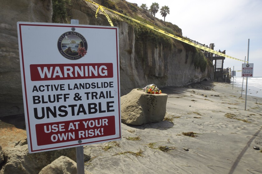 One of several warning signs is posted next to the debris left from the Aug. 3 bluff collapse, which killed three women, near the Grandview beach access stairway in Leucadia. A bouquet of flowers was placed one of the chunks of sand stone.