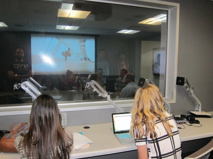 User Upload Caption: San Diego State University business students sit in the observation room to watch students making a sales presentation on the other side of a two-way mirror.