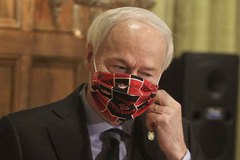"""FILE - In this April 27, 2020, file photo, Gov. Asa Hutchinson takes off his Arkansas Razorbacks facemark as he arrives for the daily coronavirus briefing at the state Capitol in Little Rock. A longtime abortion opponent who once opposed allowing gay couples to be foster parents, Gov. Hutchinson is the unlikeliest figure to complain about bills on the """"culture wars"""" reaching his desk. (Staton Breidenthal/The Arkansas Democrat-Gazette via AP)"""