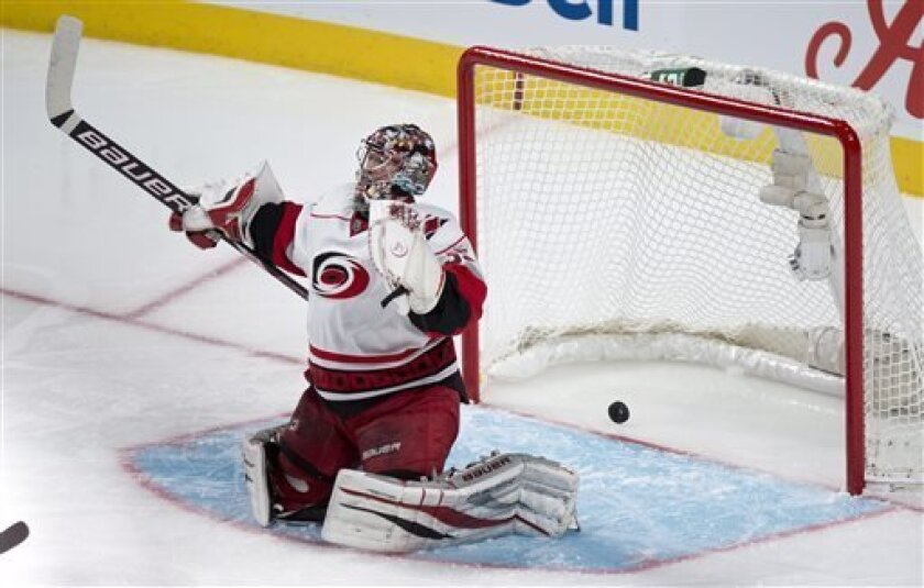The puck goes into the net past Carolina Hurricanes goalie Justin Peters on a gaol by Montreal Canadiens' Jeff Halpern during second period NHL hockey action Monday, April 1, 2013 in Montreal.  (AP Photo/ The Canadian Press, Paul Chiasson)