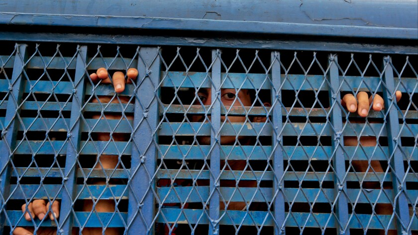 Bangladeshi men detained as part of crackdown on extremists look out from a prison van outside a court building in Dhaka on Monday.