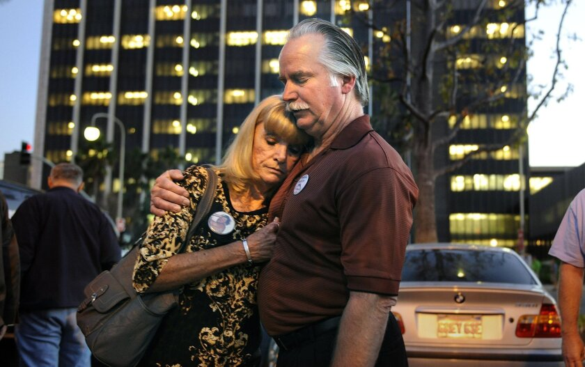 Ron and Kathy Thomas embrace at the Santa Ana courthouse after two Fullerton police officers were found not guilty in the murder of their son, Kelly.