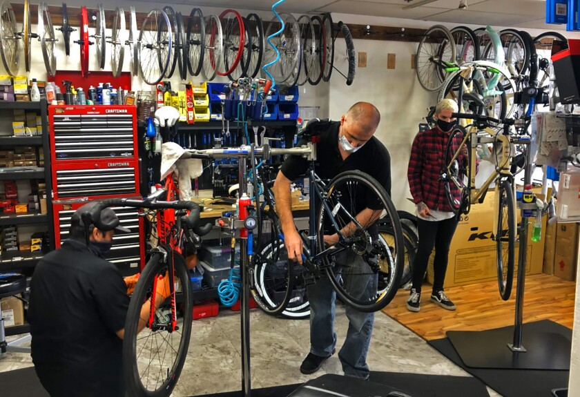 Dan Zapkoski (center), owner of Pacific Beach Bikes, works in his retail shop on Grand Avenue in Pacific Beach.