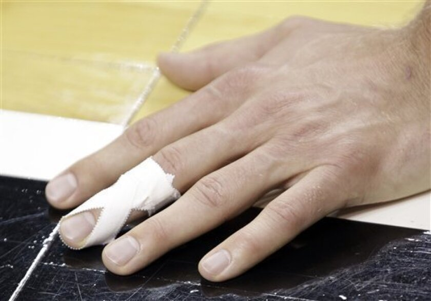 The injured left middle finger of Dallas Mavericks' Dirk Nowitzki, of Germany, is wrapped with taped during basketball practice Wednesday, June 1, 2011, in Miami. Nowitzki tore a tendon in his left middle finger during Game 1 of the NBA finals against the Miami Heat. (AP Photo/David J. Phillip)
