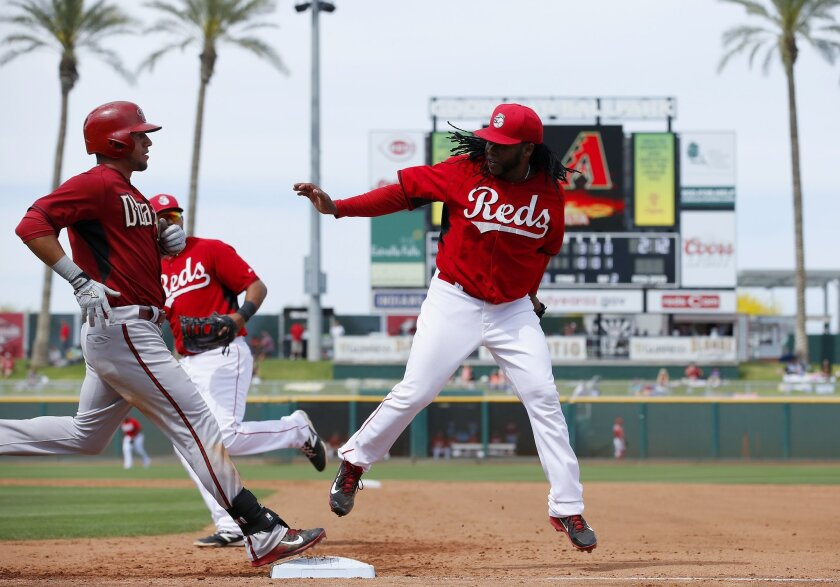 Cincinnati Reds' Johnny Cueto, right, beats Arizona Diamondbacks' David Peralta, left, to first base for an out during the fifth inning of a spring training baseball game Wednesday, April 1, 2015, in Goodyear, Ariz. The Diamondbacks defeated the Reds 3-0. (AP Photo/Ross D. Franklin)