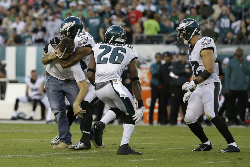 Philadelphia Eagles' Nolan Carroll (23) tackles a fan that ran onto the field during the second half of an NFL football game against the Dallas Cowboys, Sunday, Sept. 20, 2015, in Philadelphia. (AP Photo/Matt Rourke)