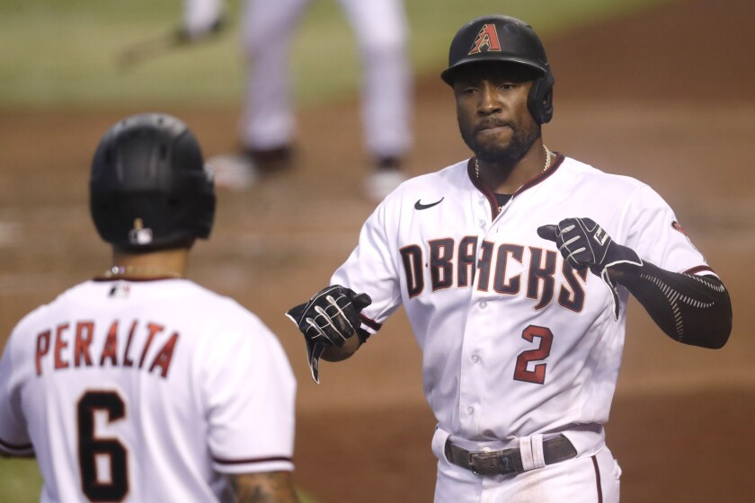 Arizona Diamondbacks' Starling Marte (2) celebrates scoring on a double by Christian Walker with teammate David Peralta (6) during the sixth inning of a baseball game against the Houston Astros Thursday, Aug. 6, 2020, in Phoenix. (AP Photo/Matt York)