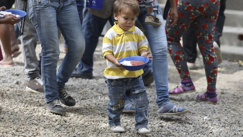 A boy walks to a nearby table with a plate of food at a migrant shelter near Cucuta, Colombia, on the border with Venezuela on Feb. 18, 2019. The shelter's director says they serve about 4,500 lunches per day, mostly to Venezuelan migrants.