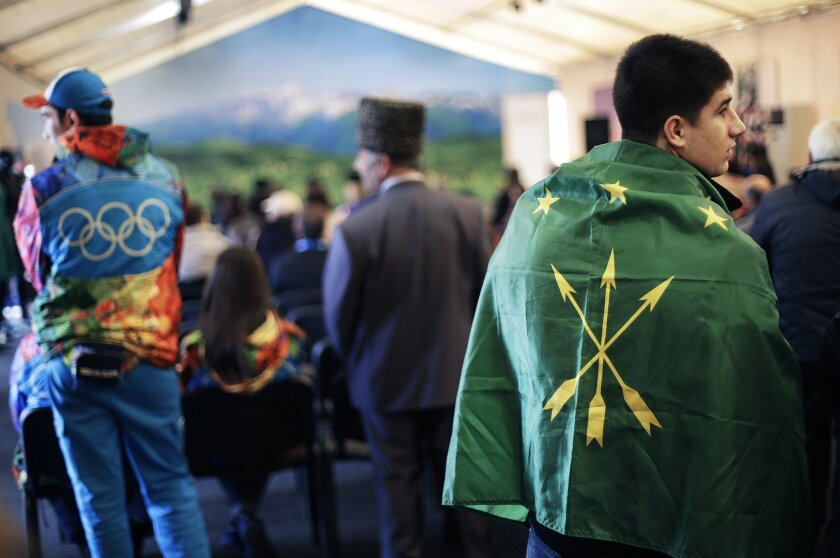 Timur Achmizov, right, wears the Circassian flag draped over his shoulders as he attends a folk theater troupe performance at the Circassian House in Olympic Park at the 2014 Winter Olympics in Sochi, Russia, Friday Feb. 14, 2014. The Circassian House was hastily erected by Olympic organizers after regional authorities belatedly acknowledged that the Olympic sites were built on what was once Circassian land. (AP Photo/David Goldman)