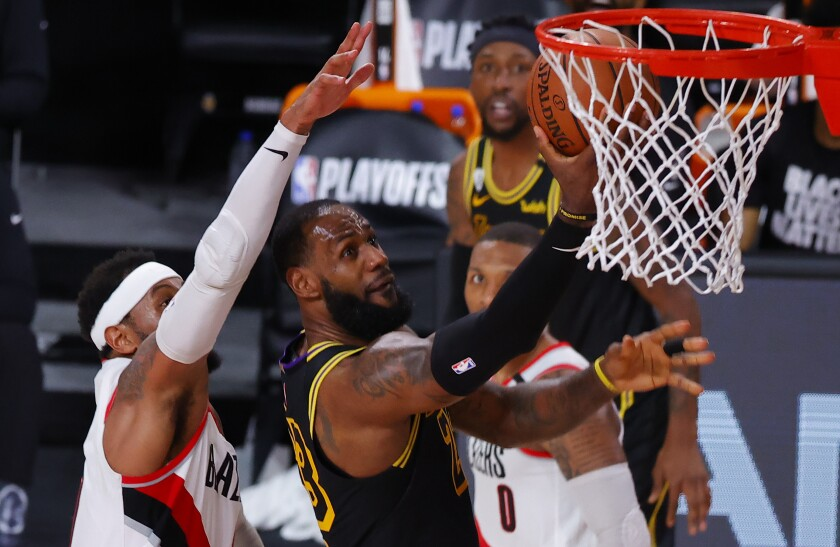 Lakers forward LeBron James shoots in front of Portland Trail Blazers forward Carmelo Anthony.