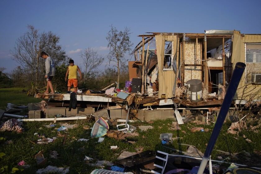 Aiden Locobon, left, and Rogelio Paredes look through the remnants of their family's home destroyed by Hurricane Ida, Saturday, Sept. 4, 2021, in Dulac, La. (AP Photo/John Locher)
