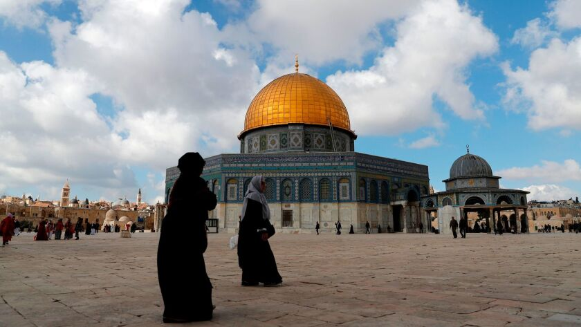 Palestinian Muslim worshipers walk past the Dome of the Rock mosque at Al Aqsa compound in Jerusalem's Old City on Dec. 15, 2017.