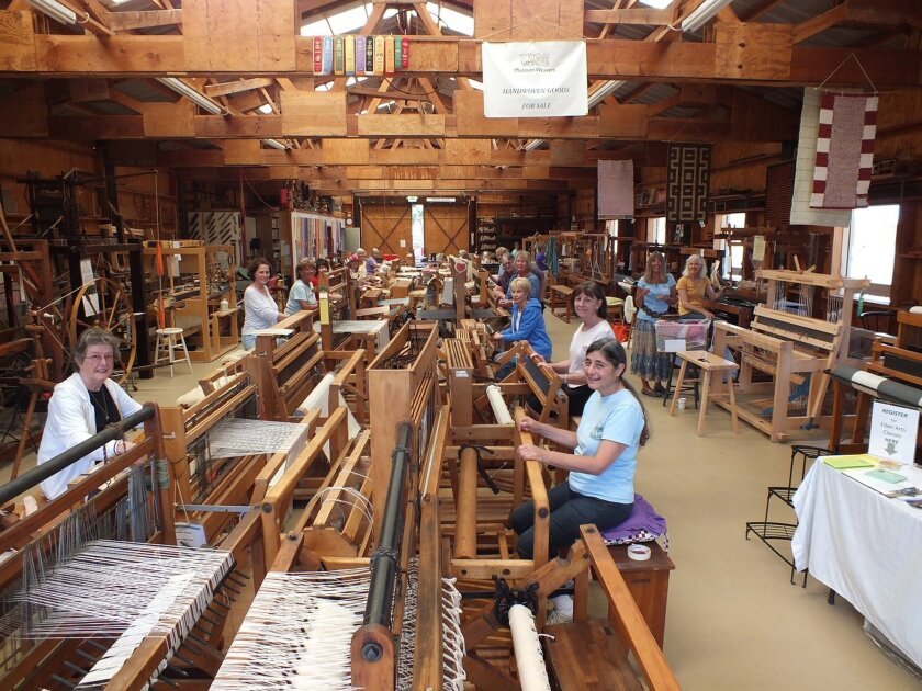 Weavers in the barn at the Antique Gas and Steam Engine Museum in Vista. Because the looms are donated, the collection is eclectic and interesting.