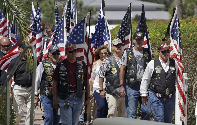 A motorcycle group carries American flags during an open funeral service for U.S. Army veteran Edward K. Pearson Tuesday, Oct. 1, 2019, at the Sarasota National Cemetary in Sarasota, Fla. Pearson has no family so his funeral home sent out a request on social media for the public to attend the service. (AP Photo/Chris O'Meara)